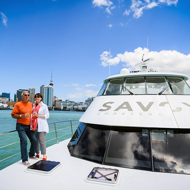 A couple enjoing a cruise with Auckland city in the background