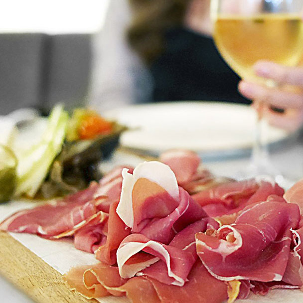 Platter of cured meats with a glass of white wine