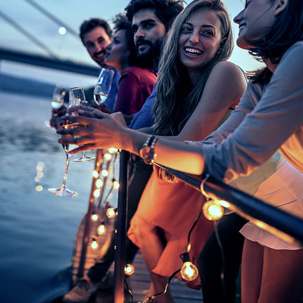 Group of people leaning on railing, celebrating with drinks on a private boat.